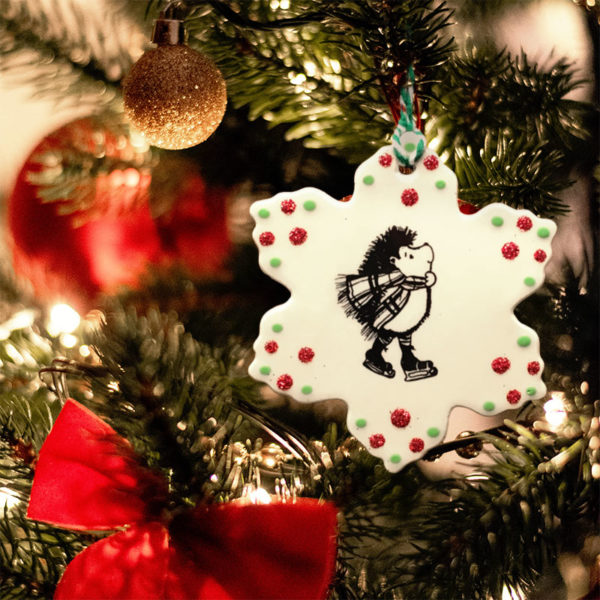 Handmade star-shaped ceramic ornament with a drawing of a hedgehog on ice skates. He's wearing a hand knitted scarf and having a great time! Peace Love Hedgehogs