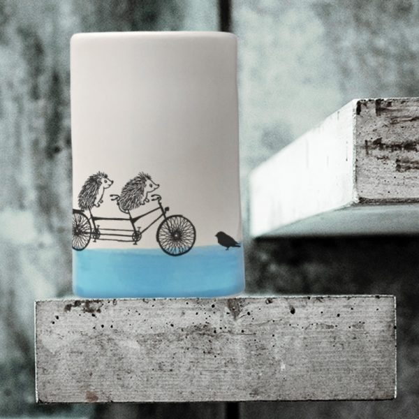 A handmade tumbler with a drawing of two hedgies riding a tandem bicycle. Made by the hedgehogs of Darn Pottery to celebrate the ride. Blue accent color.